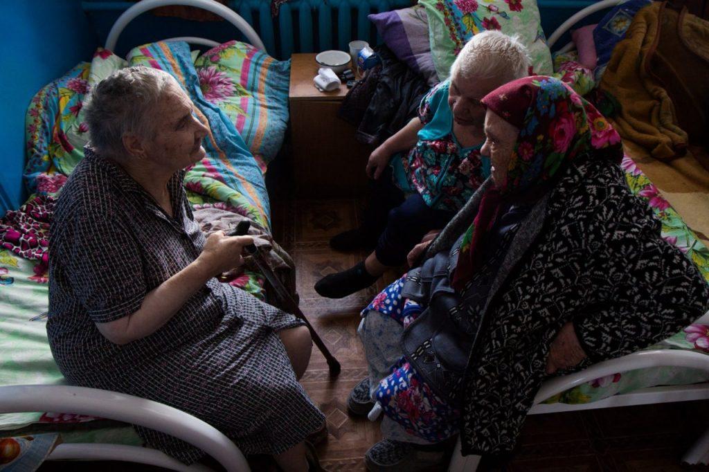 В отделение привезли новенькую (сидит ближе к окну). Валентина Ивановна (в платке), когда узнала, что в отделение попала её знакомая, пришла, чтобы поговорить с ней и познакомить с Таей. Фото Фото: Кристина Сырчикова для ТД.