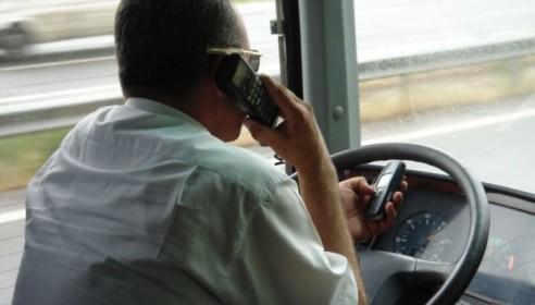 Водитель автобуса говорит по телефону