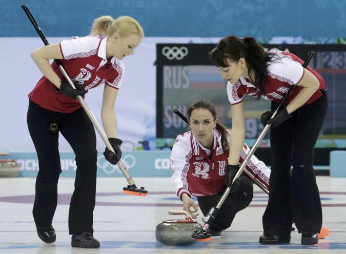 Russia's skip Sidorova delivers a stone as second Saitova and lead Galkina prepare to sweep during their women's curling round robin game against Switzerland in the Ice Cube Curling Centre at the Sochi 2014 Winter Olympic Games