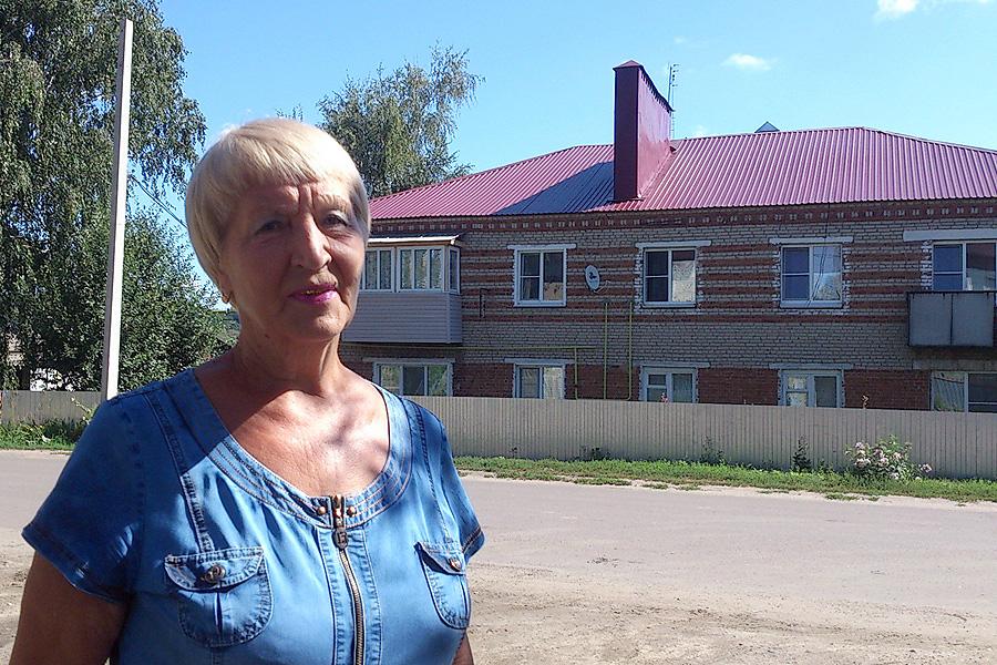 Нина Перекальская на фоне отремонтированной двухэтажки