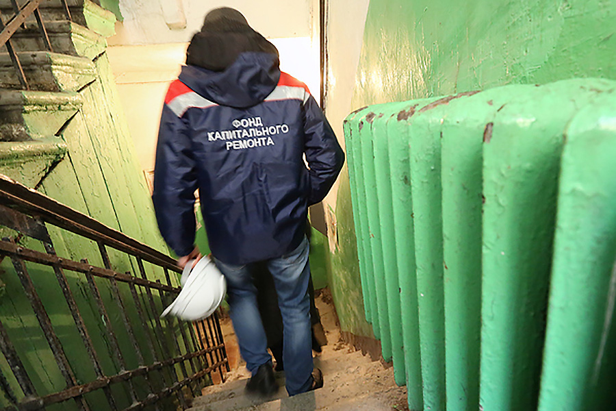Сотрудник фонда капитального ремонта в старом подъезде жилого дома.